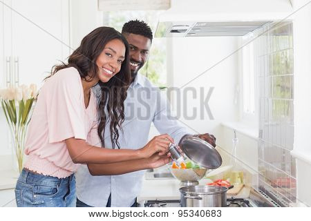 Happy couple cooking food together at home in the kitchen