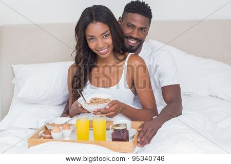 Relaxed couple having breakfast in bed together at home in bedroom