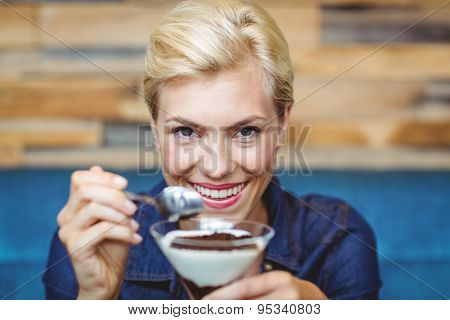 Portrait of a smiling blonde holding a chocolate goblet