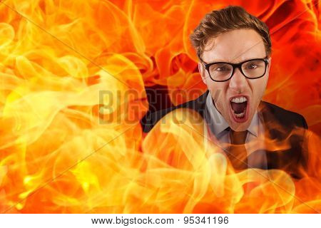 Young angry businessman shouting at camera against fire