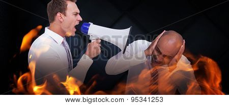 Businessman yelling with a megaphone at his colleague against dark grey room