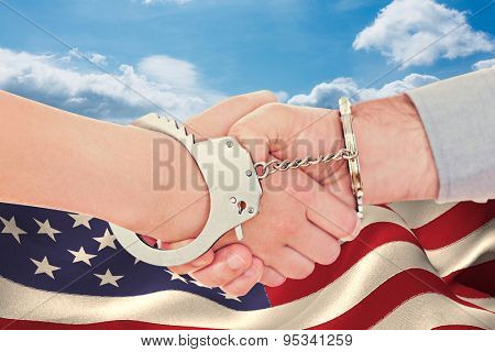 Handcuffed business people shaking hands against blue sky