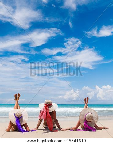 Three girls  wearing a bikini and sun hat sitting on a deserted tropical beach in Bali