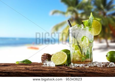 Exotic summer drink served on wooden planks. Blur beach as background