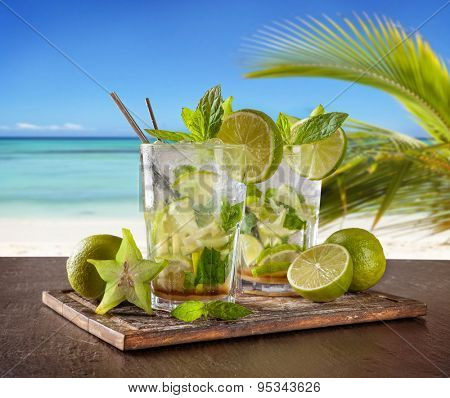 Exotic summer drinks served on stone. Blur beach as background