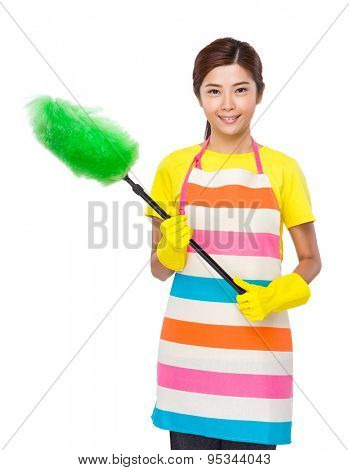 Young Housewife using duster with plastic gloves