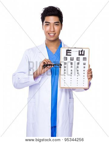 Optician holding with eye chart and glasses