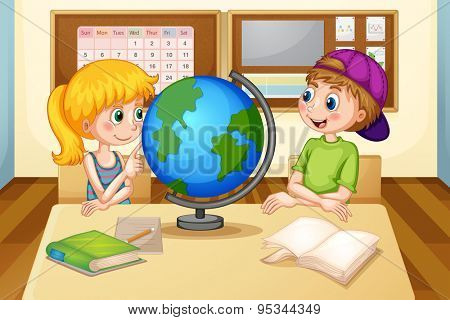 Boy and girl looking at the globe in classroom