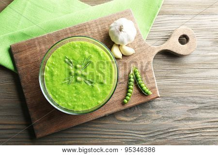 Green pea soup in glass bowl on wooden cutting board, top view