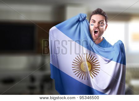 Fan holding the flag of Argentina at home