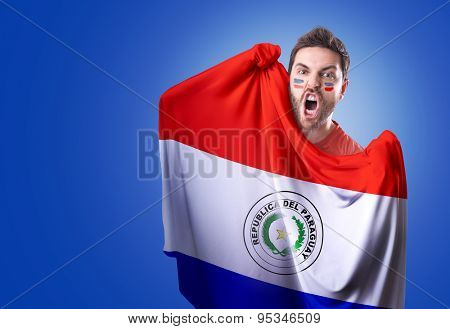 Fan holding the flag of Paraguay on blue background