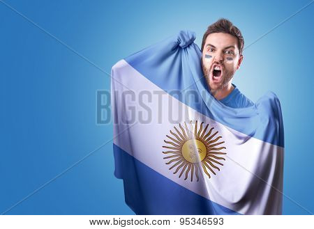 Fan holding the flag of Argentina on blue background