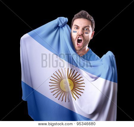 Fan holding the flag of Argentina on black background