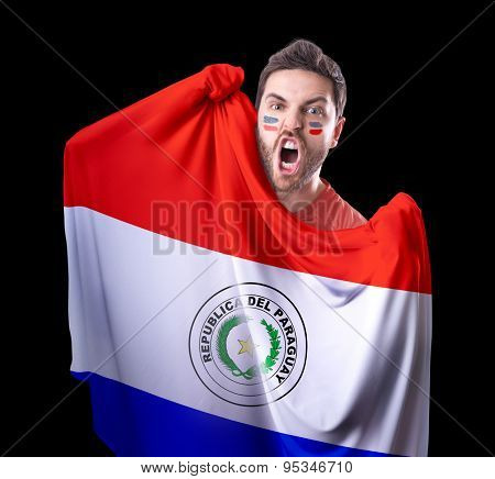 Fan holding the flag of Paraguay on black background