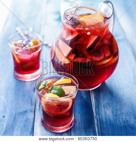 sangria with fruits and mint garnish in cups and pitcher in background