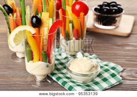 Snack of vegetables in glassware on wooden table, closeup