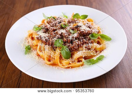 Pasta Bolognese with parmesan and basil on table close up