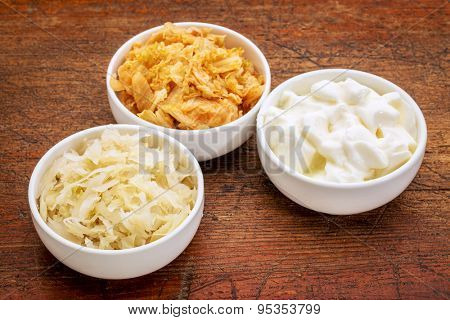 sauerkraut, kimchi and yogurt - popular probiotic fermented food - three ceramic bowl against rustic wood