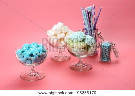 Fluffy candies in glassware on pink background