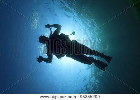 Scuba diver silhouette underwater