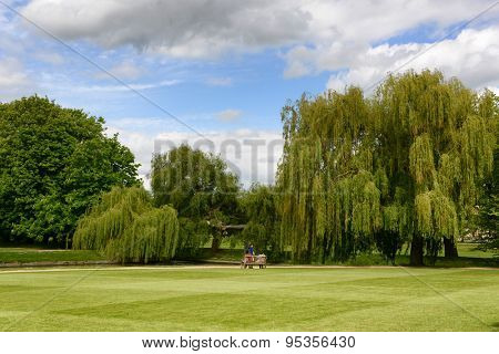 CAMBRIDGE, ENGLAND - MAY 13: Scenic View of Lone Bench Amongst Lush Green Park Setting on Grounds of Trinity College, Cambridge University, England on May 13, 2015
