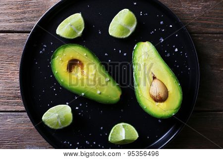 Sliced avocado with lime and salt on metal plate on wooden table background