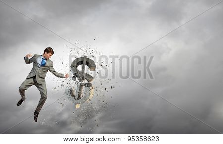 Young businessman craching with fist dollar sign