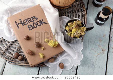 Dried herb with nutmeg and book on table close up