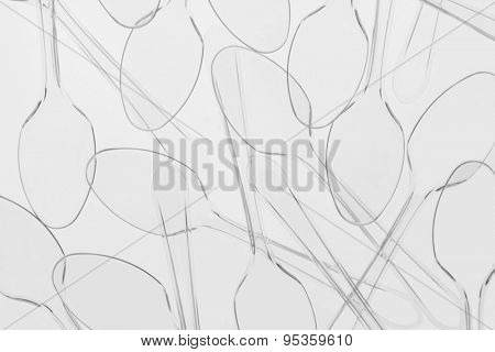 An abstract arrangement of clear plastic spoons. Backlit filling the frame.
