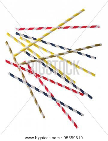 Random striped drinking straws backlit on a white surface. Red, blue, yellow, and green striped paper straws are represented.
