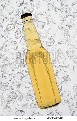 A single bottle of beer backlit on a bed of ice. The bottle has no label. Vertical Format