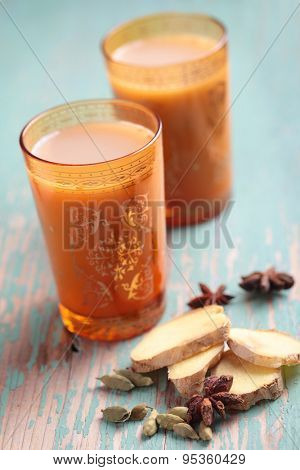 Masala chai tea in yellow glasses and spices