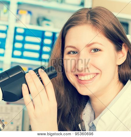 technician in the laboratory using a microscope, girl smiling