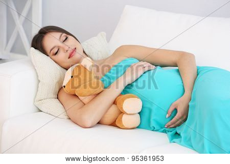 Pregnant woman lying on sofa in room