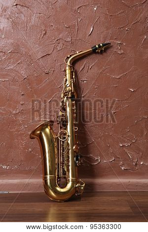 Golden saxophone on brown wall background