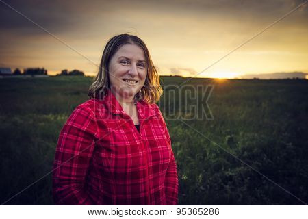 Sunset. Mature woman standing on a meadow in the rays of the setting sun. LOMO effect