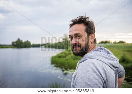 Evening twilight. Portrait of a mature man in the river landscape background.