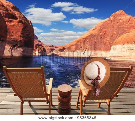 Waves from the boat cut through the Lake Powell on the Colorado River. At the stern of the vessel are two deck chairs. On the back of one hanging elegant ladies straw hat.