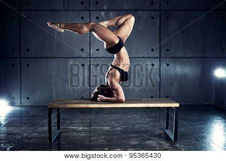 Strong woman bodybuilder standing upside down on table on wall background.