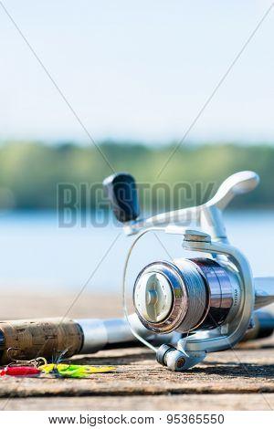fishing rod on jetty close to lake