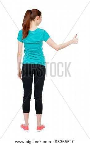 Back view of  woman thumbs up. Rear view people collection. backside view of person. Isolated over white background. slender blonde in a jeans shows the symbol of success or hitchhiking