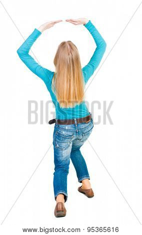 back view woman protects hands from what is falling from above. woMan holding heavy load  Isolated over white background. Girl in blue T-shirt covering his head with his hands on top something falling