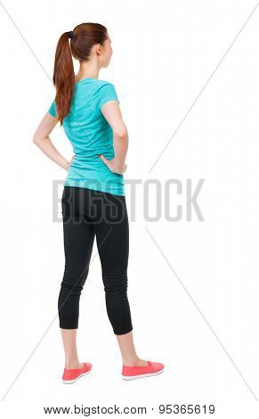 back view standing young beautiful  woman. girl  watching. Rear view people. backside view person. Isolated over white background. Sports girl is putting her hands on waist and looking to right