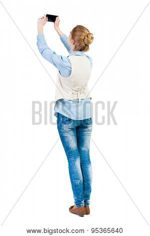back view of standing young beautiful  woman  in vest and using a mobile phone. girl  watching. Isolated over white background. Girl in sleeveless photographs on the phone at the top of the object.