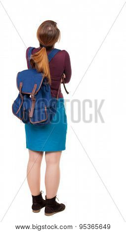 Back view of  woman with backpack looking up. Standing young girl. Rear view people collection.   girl in a blue skirt and a burgundy sweater with a blue backpack standing arms folded looking up