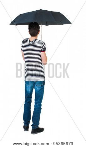 Back view man in jeans under an umbrella. Standing young guy. Rear view people collection. backside view person.  Isolated over white background. guy in the striped shirt standing under black umbrella