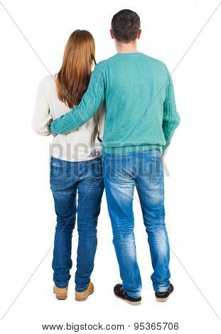 Back view of young embracing couple (man and woman) hug and look into the distance.   backside view of person.  Isolated over white background. Man hugging his right hand girl in a white blouse.