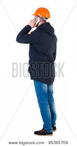 Backview of an engineer in construction helmet stands and using a mobile phone. Standing young guy.  backside view person.  Isolated over white background. Engineer is a businesswoman talking on phone