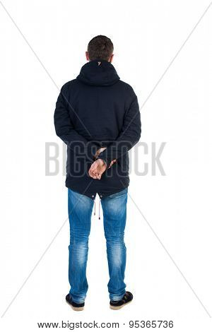 Back view handsome man in winter jacket  looking up.   Standing young guy in parka. Rear view people collection. backside view person.  . Man in warm jacket put his hands behind his back and standing
