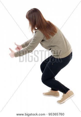 Back view of  woman thumbs up. Rear view people collection. backside view of person. slender blonde in a jeans shows the symbol of success or hitchhiking. To the bottom of the girl showing a thumbs up